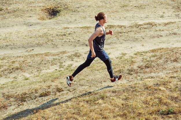Бег спорт. бегущий человек спринте открытый в живописной природе. приспособьте мускулистую мужскую спортивную тренировочную тропу, бегущую для пробега марафона спортивный здоровый атлетик работает в сжатой одежде в спринте