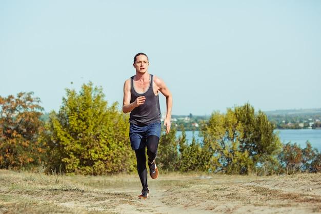 スポーツを実行しています。風光明媚な自然の中で屋外全力疾走の男性ランナー。マラソンランニングの筋肉男性アスリートトレーニングトレイルをフィットします。スプリントの圧縮服でワークアウトフィットのスポーティなアスレチック男