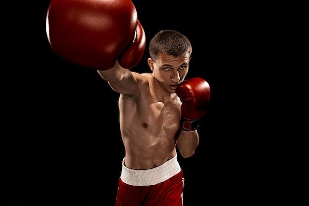 男性のボクサーが黒に劇的なエッジの効いた照明でボクシング