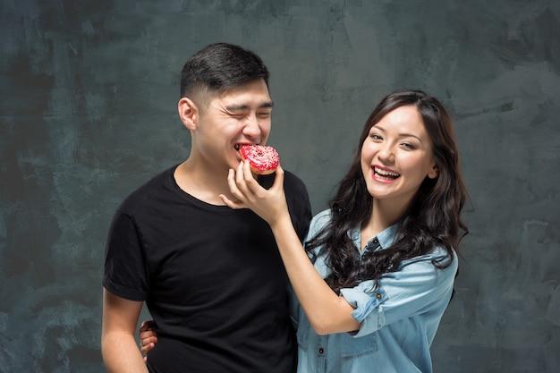 若いアジアのカップルは甘いカラフルなドーナツの食事を楽しむ