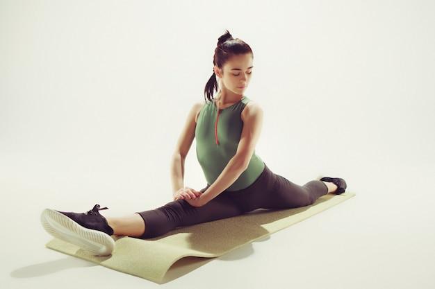Красивая молодая стройная женщина делает упражнения на растяжку в тренажерном зале на белом