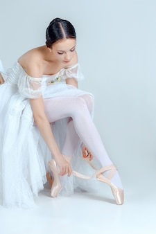 Профессиональная балерина надевает балетные туфли