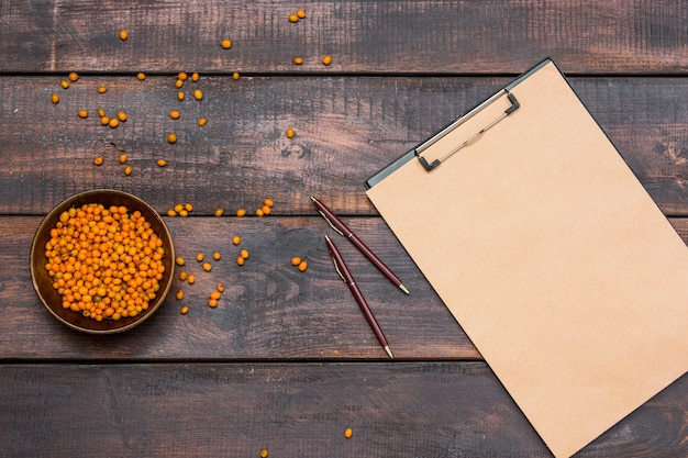 ノートブック、木製のテーブルに新鮮なクロウメモドキの果実とオフィスデスクテーブル