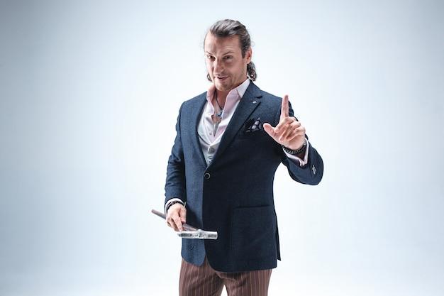 Зрелый бородач в костюме держит трость. изолированные на синем.