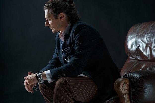 グレーのスーツを着た大人のスタイリッシュな男性。肘掛け椅子に座っている実業家