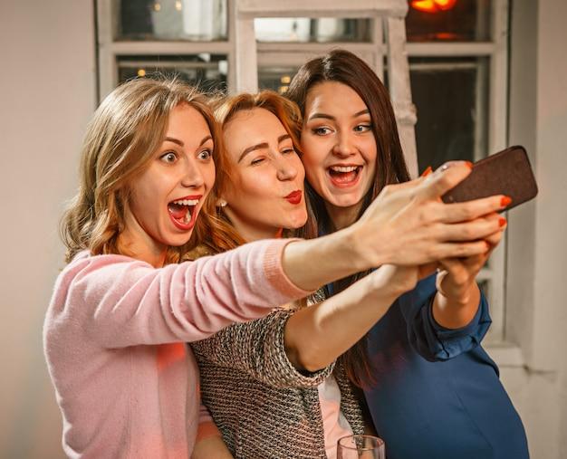 ビールと女の子が自分撮り写真を作ると夜の飲み物を楽しんでいる友人のグループ