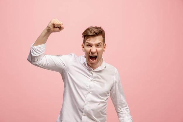 叫び、憎しみ、怒り。ピンクで叫んで泣いている感情的な怒っている人。感情的な若い顔。男性の半身像。人間の感情、表情のコンセプト。流行色