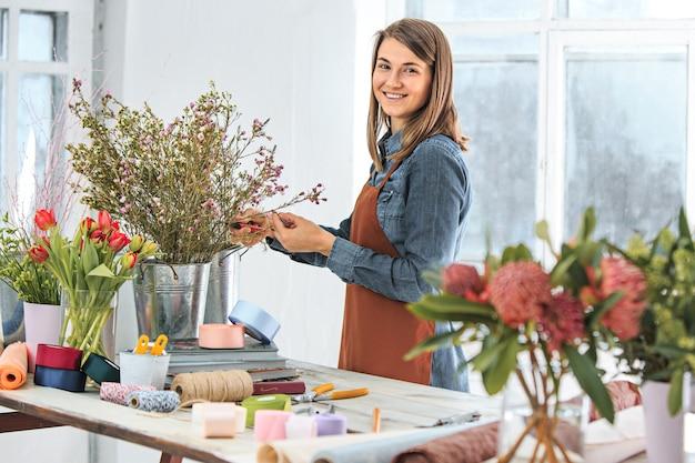 Молодая девушка делает букет из разных цветов