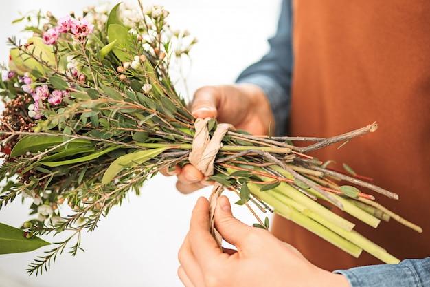 Флорист делает букет из разных цветов