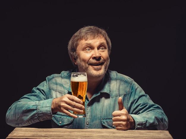 ビールのグラスとデニムシャツの男の笑みを浮かべてください。