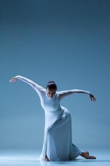 Классическая балерина танцует на синем