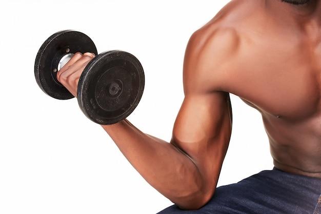 Сильный и мускулистый парень с гантелями на белом