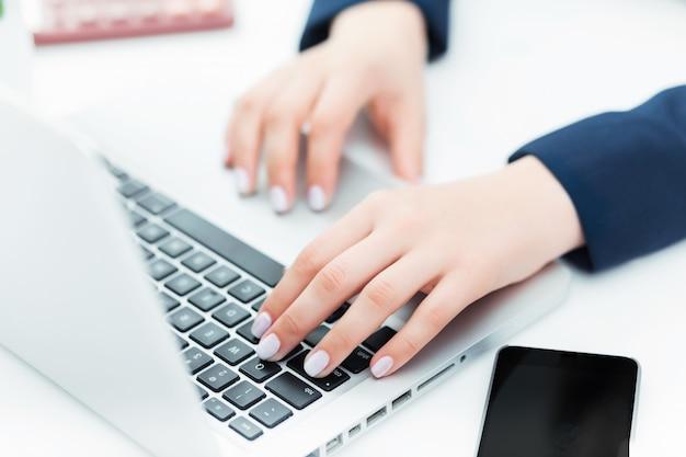 女性は彼女のラップトップコンピューターのキーボードを手します。
