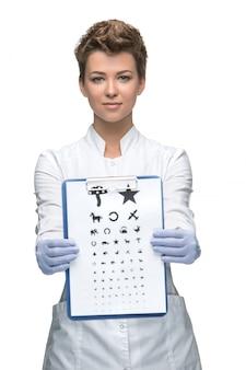 視力検査表を持つ若い女性眼科医