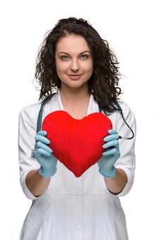 赤いハートを保持しているきれいな女性医師