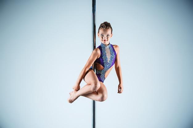 パイロンでアクロバティックな演習を実行する強くて優雅な若い女の子