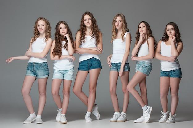 Модные девушки стояли вместе и глядя на камеру на сером фоне студии