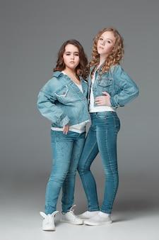 Полная длина молодой стройной девушки в джинсовых джинсах на сером фоне