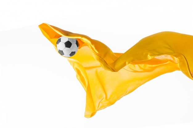 サッカーボールと白いスタジオの背景に分離または分離された滑らかなエレガントな透明な黄色の布。