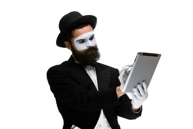 Человек с лицом пантомимы работает на ноутбуке