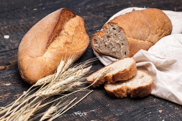 木製のテーブルに素朴なパン。暗い背景の木