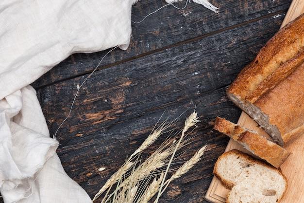 木製のテーブルに素朴なパン。フリーテキストスペースと暗い木質背景。