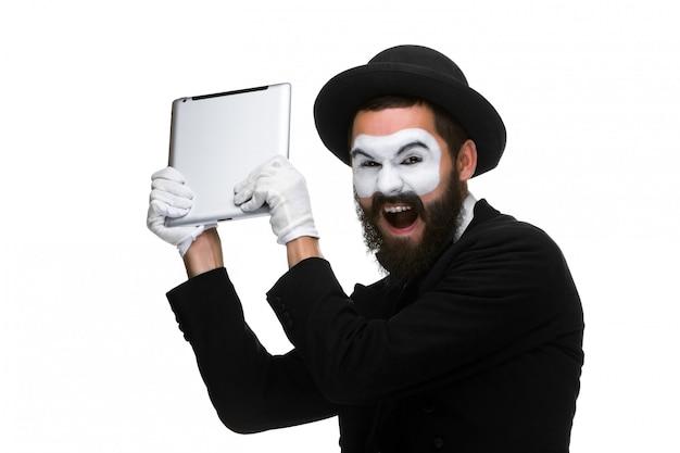 Мим, как бизнесмен бросает компьютер в ярости.