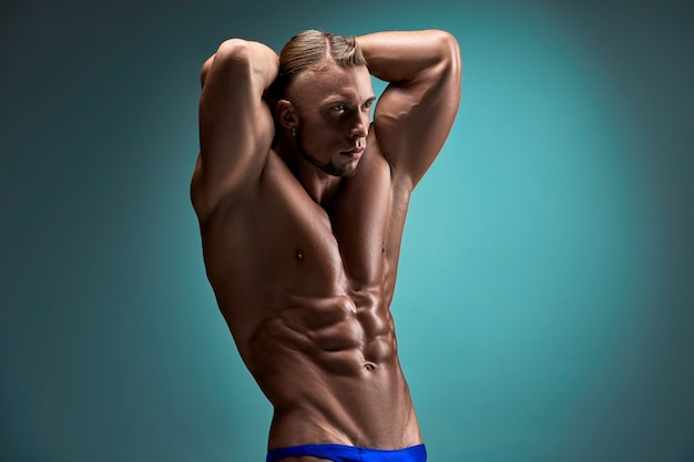 青色の背景に魅力的な男性ボディビルダー