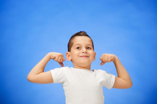 彼の上腕二頭筋を示す笑みを浮かべてスポーツ子供少年の美しさ