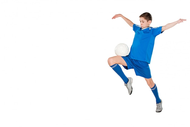 Молодой мальчик с футбольным мячом делает летающий удар