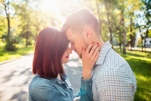 公園に立って、明るい晴れた日に笑って幸せな若いカップル