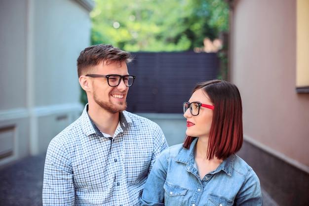 街の通りに立って、明るい晴れた日に笑って幸せな若いカップル