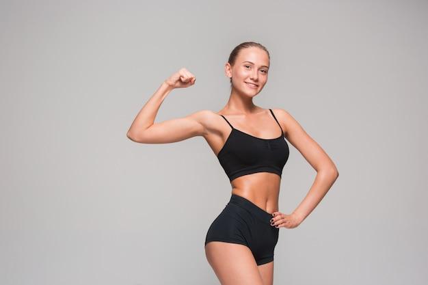 灰色の筋肉の若い女性の運動選手