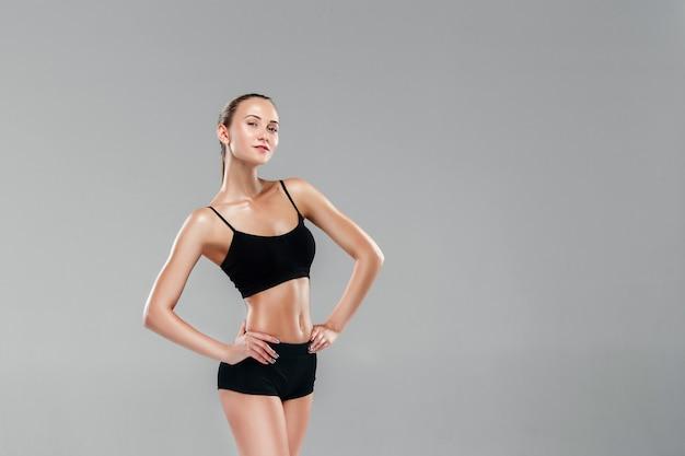 Мускулистые молодая женщина спортсменка на сером