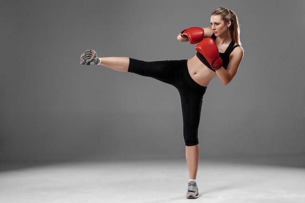 美しい女性は灰色の背景にボクシング