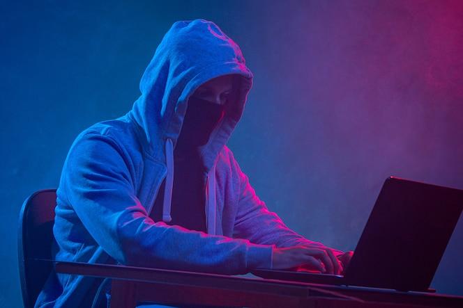 Компьютерный хакер с капюшоном ворует информацию с ноутбука