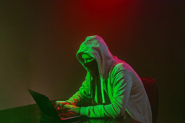 ラップトップで情報を盗むフード付きのコンピューターハッカー