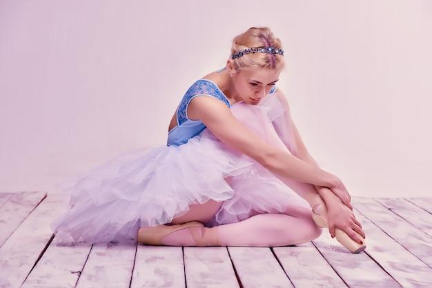 Уставшая балерина сидит на деревянном полу