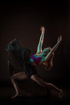 黒い壁に踊るベージュのドレスの若い美しいダンサー