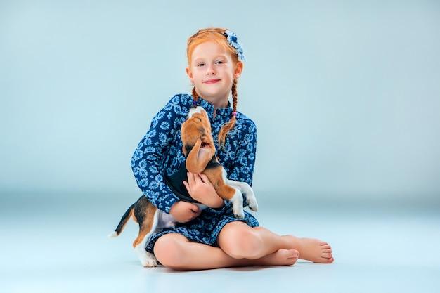 幸せな少女と灰色の壁にビーグル犬の子犬
