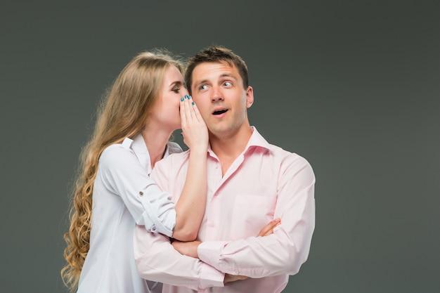 Портрет молодой пары, стоящей на серой стене
