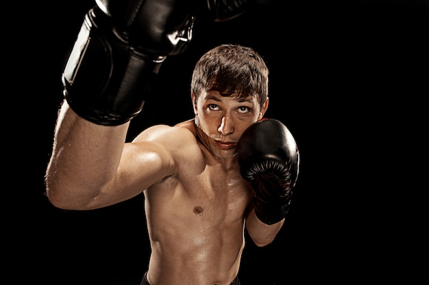 劇的なエッジの効いた照明とパンチングバッグの男性ボクサーボクシング