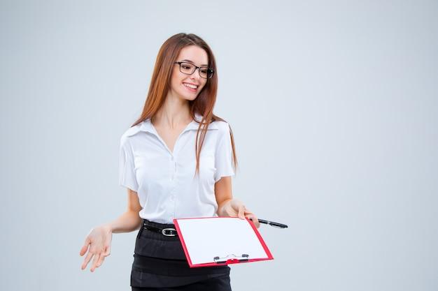 Улыбающаяся молодая деловая женщина с ручкой и планшетом для заметок на серой стене