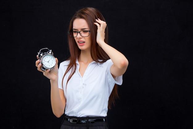 目覚まし時計を持つ若いビジネス女性