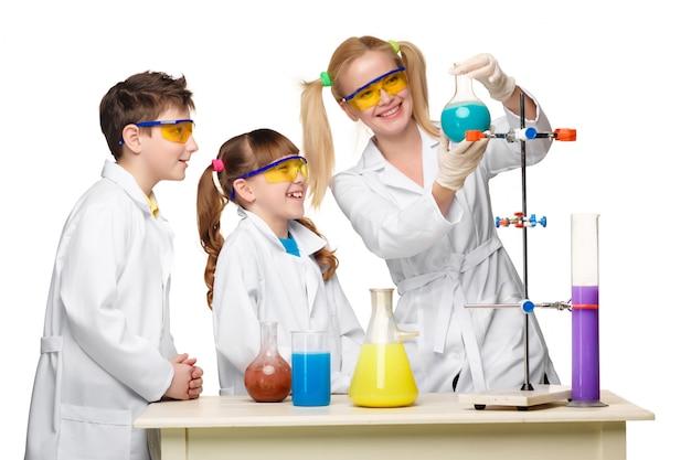 Подростки и учитель химии на уроке проводят эксперименты