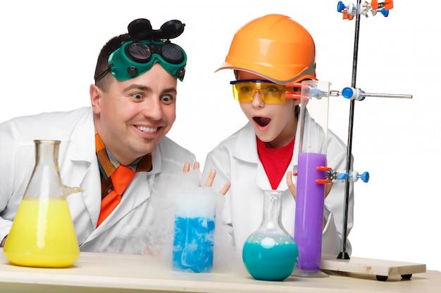 Подросток и учитель химии на уроке проводят эксперименты