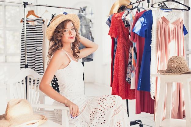 Привлекательная женщина примеряет шляпу. счастливых летних покупок.