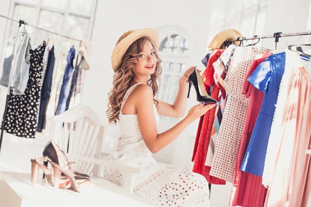 Молодая милая женщина выбирая и примеряя модельные ботинки на магазине