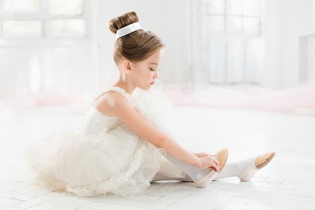 Маленькая балерина в белой пачке в классе на балете