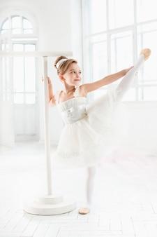 チュチュのバレリーナ少女。白いスタジオでクラシックバレエを踊る愛らしい子。